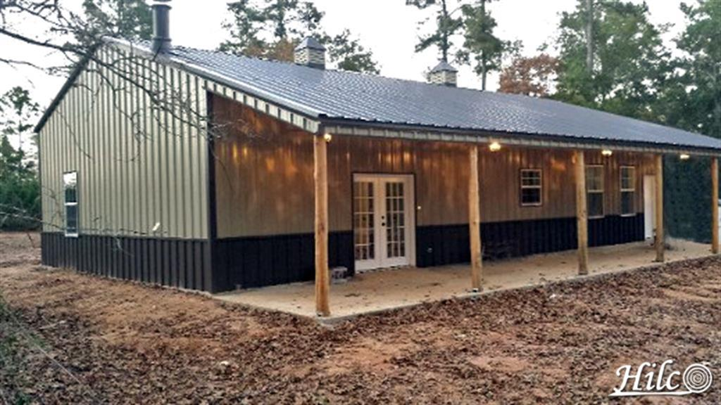 Metal Barndominium with Rustic Columns on Porch